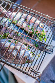Fish stuffed with herbs in grilling baskets