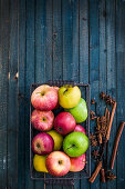 Various apples in a wire basket and spices on a blue wooden background
