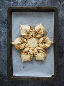 Sweet Christmas bread in a star shape with cinnamon and almonds, unbaked
