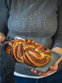 A woman holding a plaited bread with chocolate and cinnamon