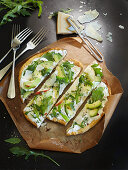 Pizza bread with cream cheese, avocado, rocket and Parmesan