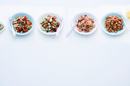 Four different salads with tomatoes