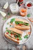 Vegan Banh mi sandwich with tofu, avocado, carrot pickles, vegan mayo and sriracha