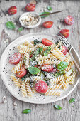 Fusilli pasta with spinach, asparagus, tomatoes, basil, pine nuts and grated parmesan cheese