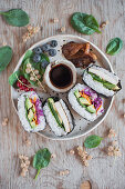 Onigirazu (Japanese sushi sandwich) - seaweed (nori), sushi rice, pickles vegetable, avocado and wasabi