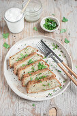 Traditional Polish potato cake served with chopped parsley and yoghurt