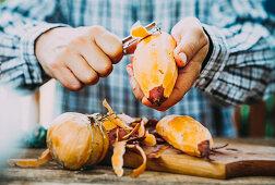 A man peeling fresh sweet potatoes