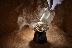 A chocolate dessert being smoked under a glass cloche