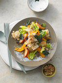 Sweet-and-sour pumpkin and apple salad with sage and raisins on fried ravioli on crispy breadcrumbs