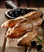 Olive baguettes wrapped in string with black olives