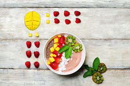 Strawberry smoothies breakfast bowl with coconut flakes, mango, strawberry and Chia seeds
