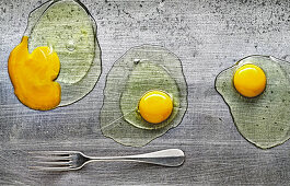 Food art: three cracked eggs on a metal surface