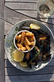 Mussels in a white wine, lemon, garlic and thyme sauce, with french fries, lemon slices, and a glass of white wine, on an outdoor table