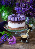 A festive blackberry cake with chocolate glaze and blue macaroons