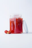 A glass of wild strawberry jam against a white background