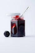 A glass of blackberry jam against a white background