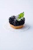 A mini tartlet with blackberries against a white background