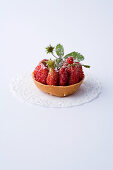 A mini tartlet with wild strawberries against a white background