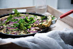 Vegan frittata with beans, peas, broccoli, mushrooms and onions
