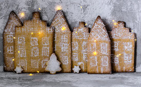 Gingerbread city with lights on concrete background