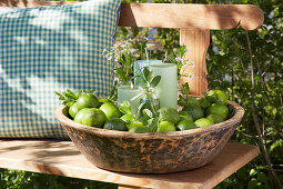 Pillar candles, posy of herbs and limes in wooden bowl