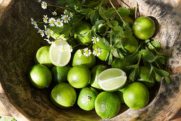 Posy of herbs and limes in wooden bowl