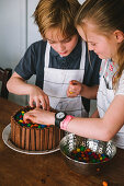A boy and a girl decorating a chocolate cake wearing white aprons