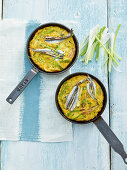 Frittata with fresh sardine fillets and spring onions in pans