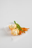 Fried rice balls filled with mozzarella, with courgette flowers on white paper
