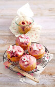 Mini raspberry cakes made from quark-oil dough decorated with icing and white fondant butterflies