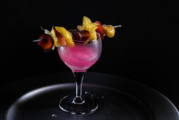 A pink drink with an exotic fruit skewer