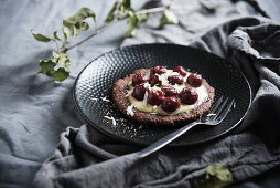 Vegan chocolate pastry with vanilla cream, sour cherries and white rice milk chocolate