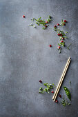 Pomegranate seeds, pea pods and chopsticks on a grey surface