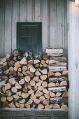 Firewood stacked against façade in winter