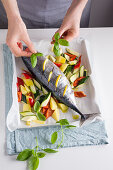 A small tuna fish with vegetables and basil on an oven tray