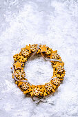Christmas wreath of gingerbread dough in the shape of stars and snowflakes, tied with a silver ribbon