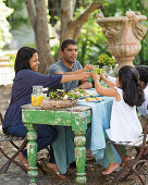 A family eating Easter Sunday lunch in a garden
