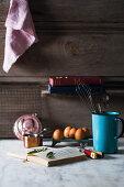 Eggs, herbs, a cookbook, and kitchen utensils