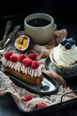 Eclair with berries and cream, and vanilla cupcake, black coffee