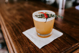 A drink with a chili pepper and herbs