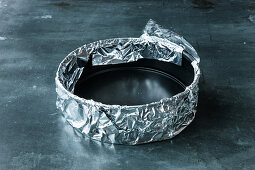 A springform tin being covered with tin foil