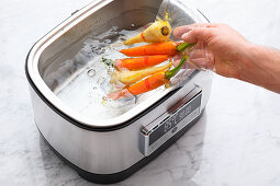 Sous vide root vegetables being placed in a sous vide cooker