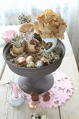 Various Easter eggs and quail eggs on cake stand and chocolate bunnies on table