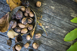 Walnuts whole and shelled on a wooden background (top view)
