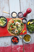 Wraps with deviled eggs, micro herbs, avocado and tomatoes (top view)