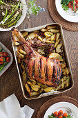 Roasted leg of lamb in a baking tray on the table along with other vegetable dishes