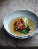 Fried pork belly in a spicy oriental broth