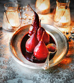 Christmas Spiced Pears poached in red wine on silver dish