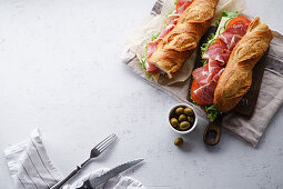 Top view of two fresh baguette sandwiches bahn-mi styled with olives, ham, sliced cheese, tomatoes and fresh lettuce