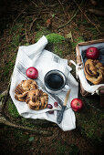 A picnic basket in a forest, filled with a vegan chocolate bun, fruit and coffee